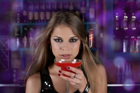 Beauty young woman portrait with a glass drinking a cocktail at a bar photo