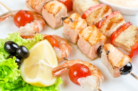 Closeup of grilled salmon and shrimps with tomatoes and peppers on bamboo sticks