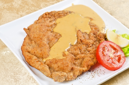 Delicious Schnitzel with lemon, tomato, lettuce and sauce  Stock Photo - 14795297