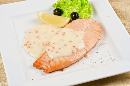 Grilled salmon steak with sauce of cheese and caviar, greens, lemon and olive photo