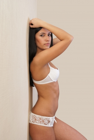Sexy girl in lingerie at wall photo