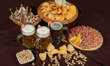 Beer and snacks set  chips, pistachio, shrimp and fish photo
