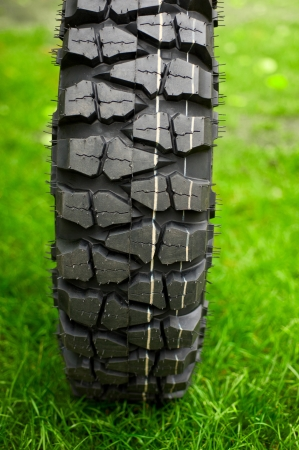 muddy tracks: Tire at green grass background