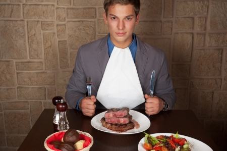 man holding a knife and a fork ready to eat a beef steak Stock Photo
