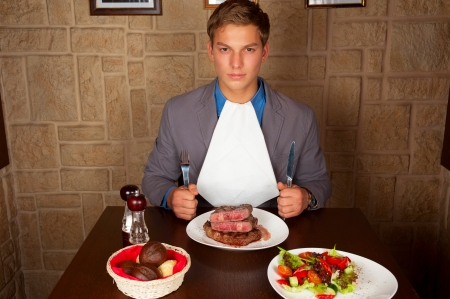man holding a knife and a fork ready to eat a beef steak photo