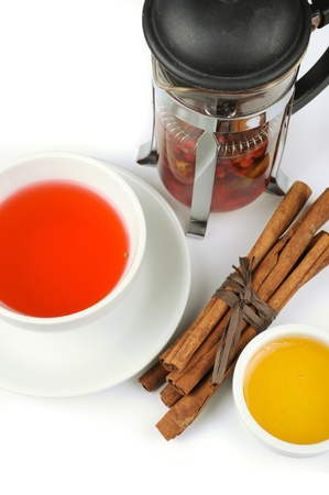 Cup of black tea from cowberry and mint with cinnamon sticks, and honey photo