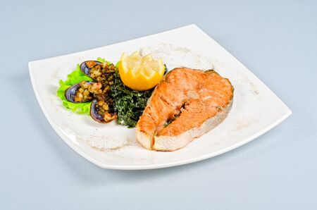 Tasty dish of salmon steak with algae mussels, lemon and kiwi photo