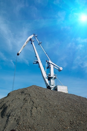 crane at heap of gravel on blue sky background photo