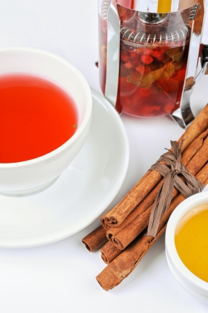 Cup of hot berries tea with cinnamon sticks, and honey Stock Photo - 17767601
