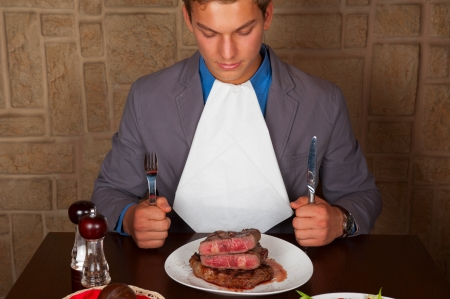 man holding a knife and a fork ready to eat a beef steak 版權商用圖片