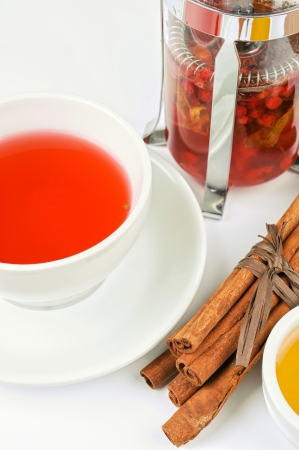 Cup of hot berries tea with cinnamon sticks, and honey photo
