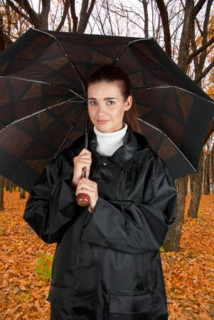 Beautiful young woman in a park with umbrella photo