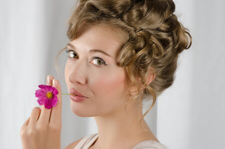 beauty woman closeup portrait with flower over grey background photo