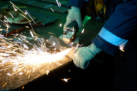 worker welding metal with sparks at factory photo