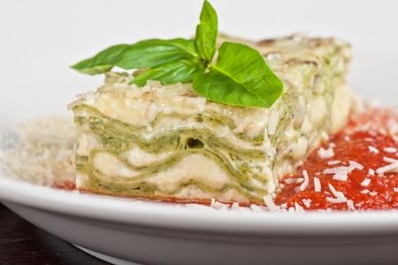 Portion of lasagna garnished with salad greens photo