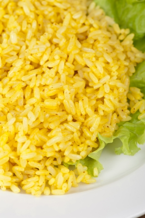 golden rice with lettuce at plate closeup photo