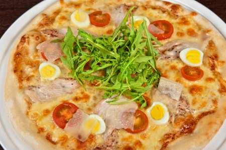 meat pizza with chicken, rukkola and eggs at the table photo