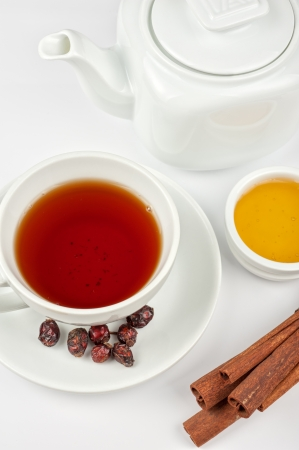 Cup of hot berries tea with cinnamon sticks, and honey Stock Photo - 21444484