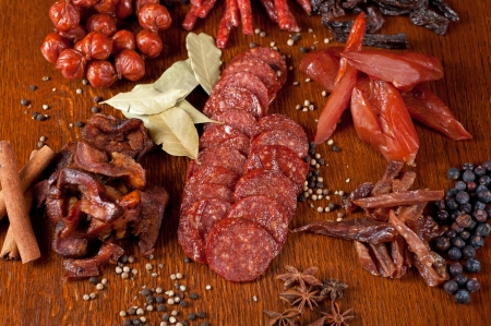 different sausage and meat on a celebratory table with spices and vegetables photo