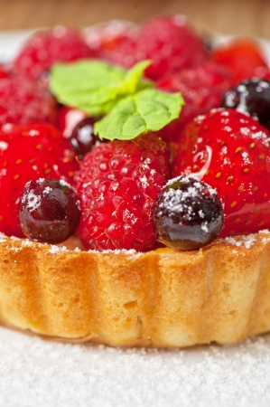 Cake with fresh berries and mint closeup photo