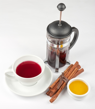 Cup of hot berries tea with cinnamon sticks, and honey Stock Photo - 23695783