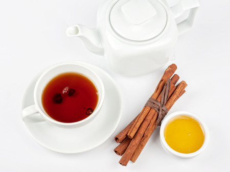 Cup of hot berries tea with cinnamon sticks, and honey Stock Photo - 24042942
