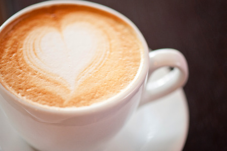 capuchino: Coffee cup with milk and heart shape