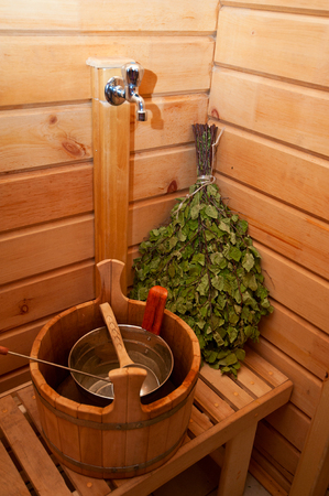 finland sauna: traditional sauna stuff -  birch whisk and a bucket Stock Photo