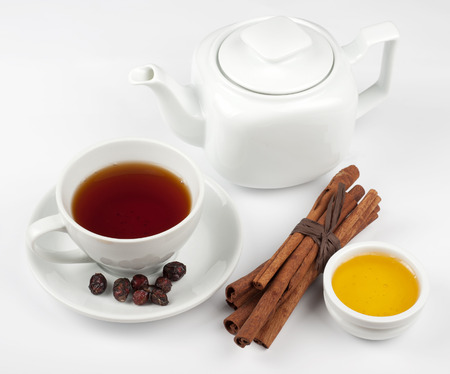 Cup of hot berries tea with cinnamon sticks and honey photo