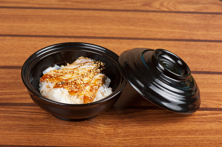Japanese cuisine, eel with rice at black plate photo