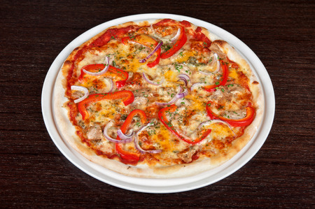 meat pizza with vegetables at the table photo