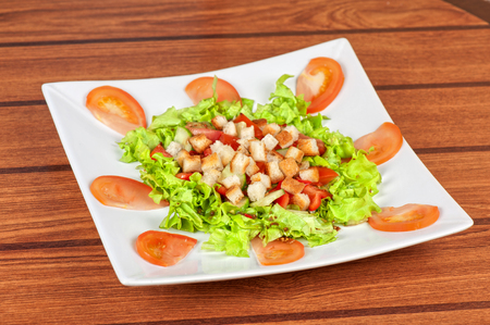 Vegetable salad with tomato, lettuce, cucumbers and crackers photo