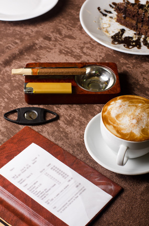 check, ashtray, cigar, lighter and coffee at restaurant table photo