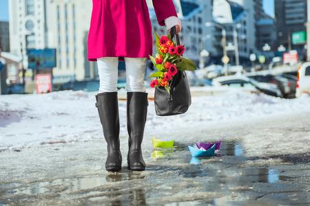 Woman wearing rain boots stay into a puddle Standard-Bild