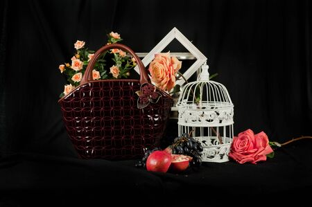 layman: Fashionable handbag  with cage fruits and flowers on black background.