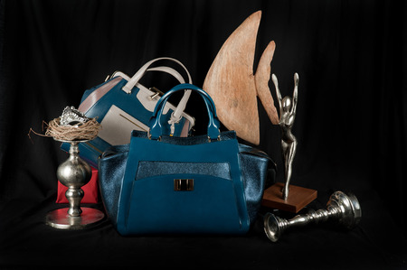 layman: Fashionable handbag  with jewelry and different items for composition on black background.