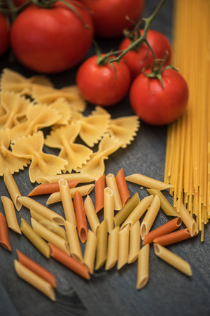 rustic food: food background on rustic wood with pasta and tomatoes