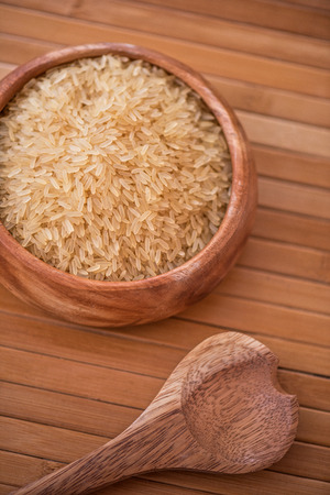 golden rice on wooden plate on wooden background photo