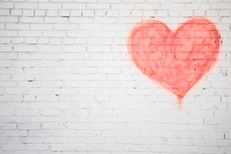 corazon en la mano: pared de ladrillo blanco con fondo rojo del corazón