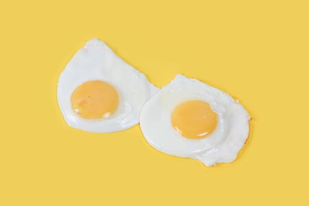 sunny side up eggs: Fried eggs on yellow background