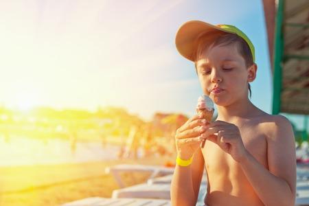 comiendo helado: Niño pequeño con helado en la playa