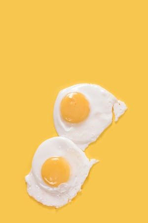 fried: Fried eggs on yellow background