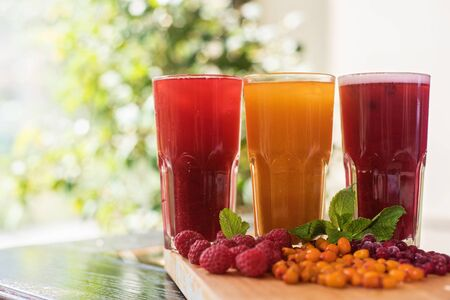 yellow to drink: set of fruit non-alcoholic drink with cranberries raspberries and sea buckthorn Stock Photo