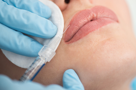Closeup of woman gets injection in her lips