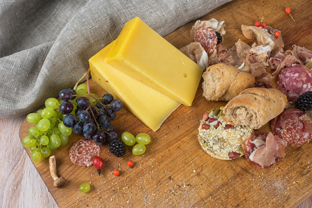 grapes and mushrooms: Fresh grapes, cheese bacon berries and salami on wooden table Stock Photo