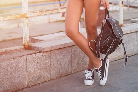 outdoor shot: closeup of woman legs in white gumshoes, outdoor shot