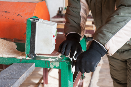 sawmill: Carpenter working at sawmill, closeup photo