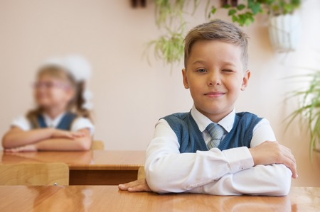 diligente: colegial feliz sentado en el escritorio, primer día en la escuela Foto de archivo