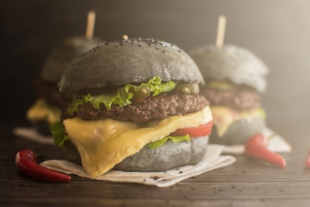 Black burger with beef meat cheese lettuce onion, tomato and sauce served on black wooden table
