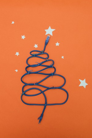 Tech New Year: fir-tree from wires on orange background